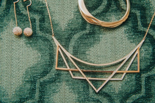 gold necklace and earrings on turquois chair