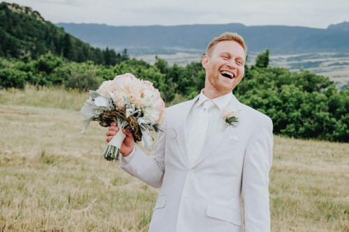 laughing groom with bouquet