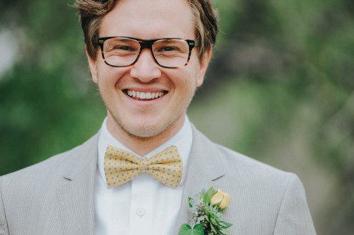groom laughing glasses yellow bow tie