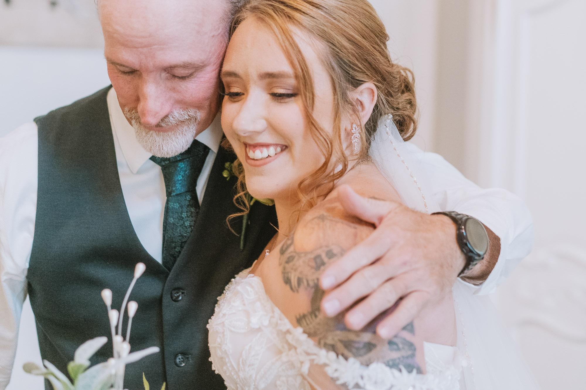 father and bride hug at wedding