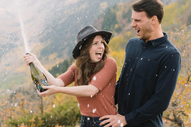 engaged couple popping champagne in Colorado mountains