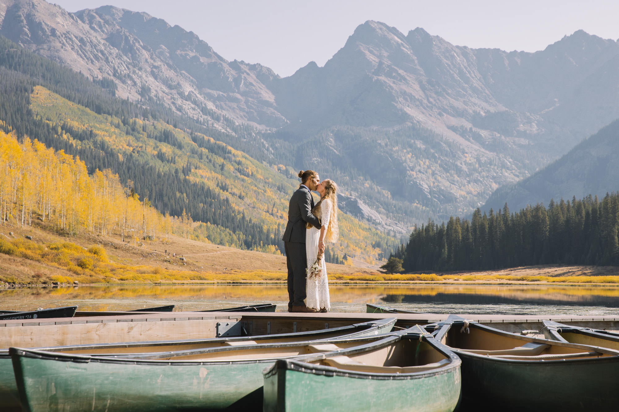 Bride and groom kissing in Colorado mountains