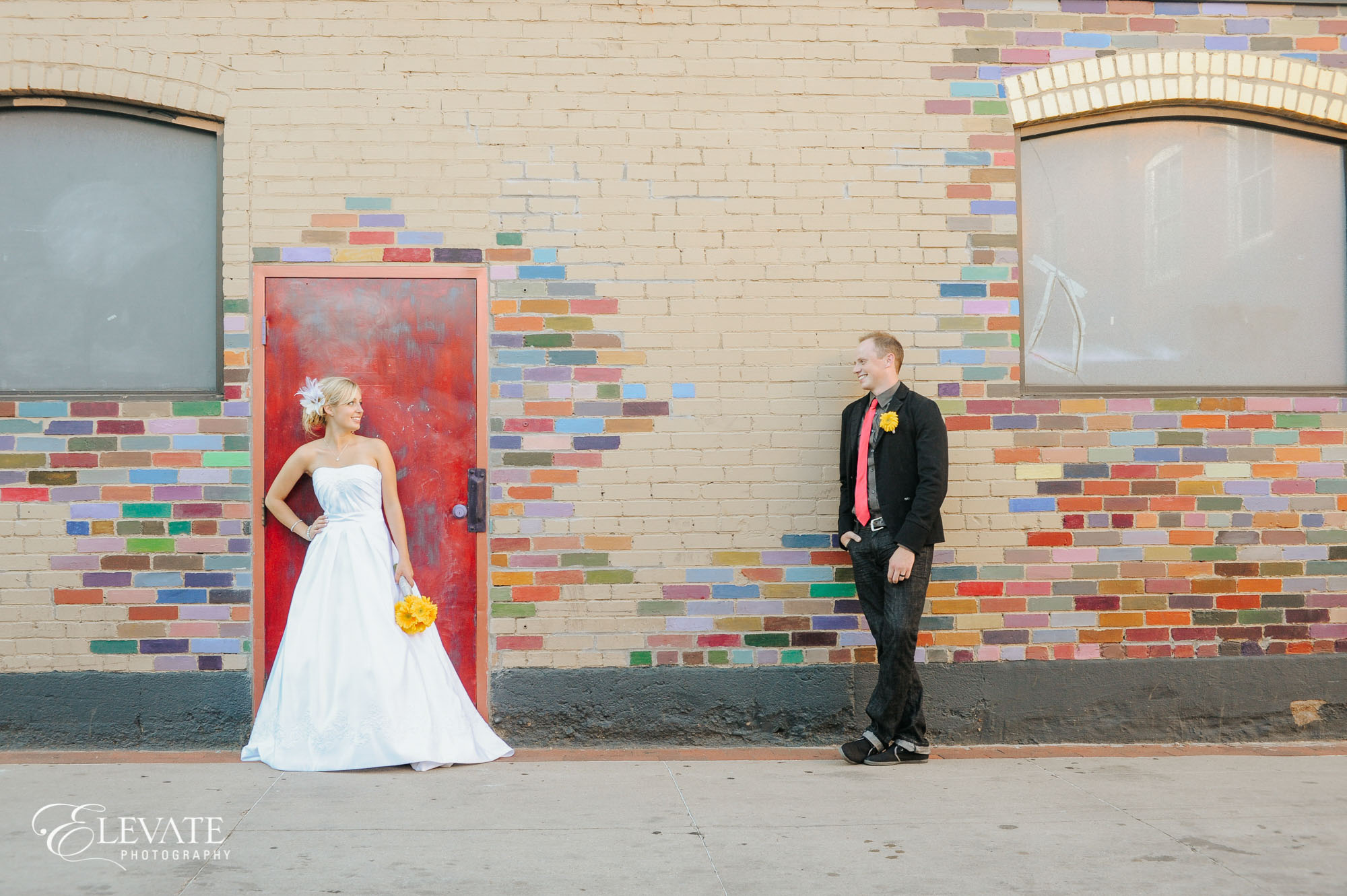 couple on colored brick wall