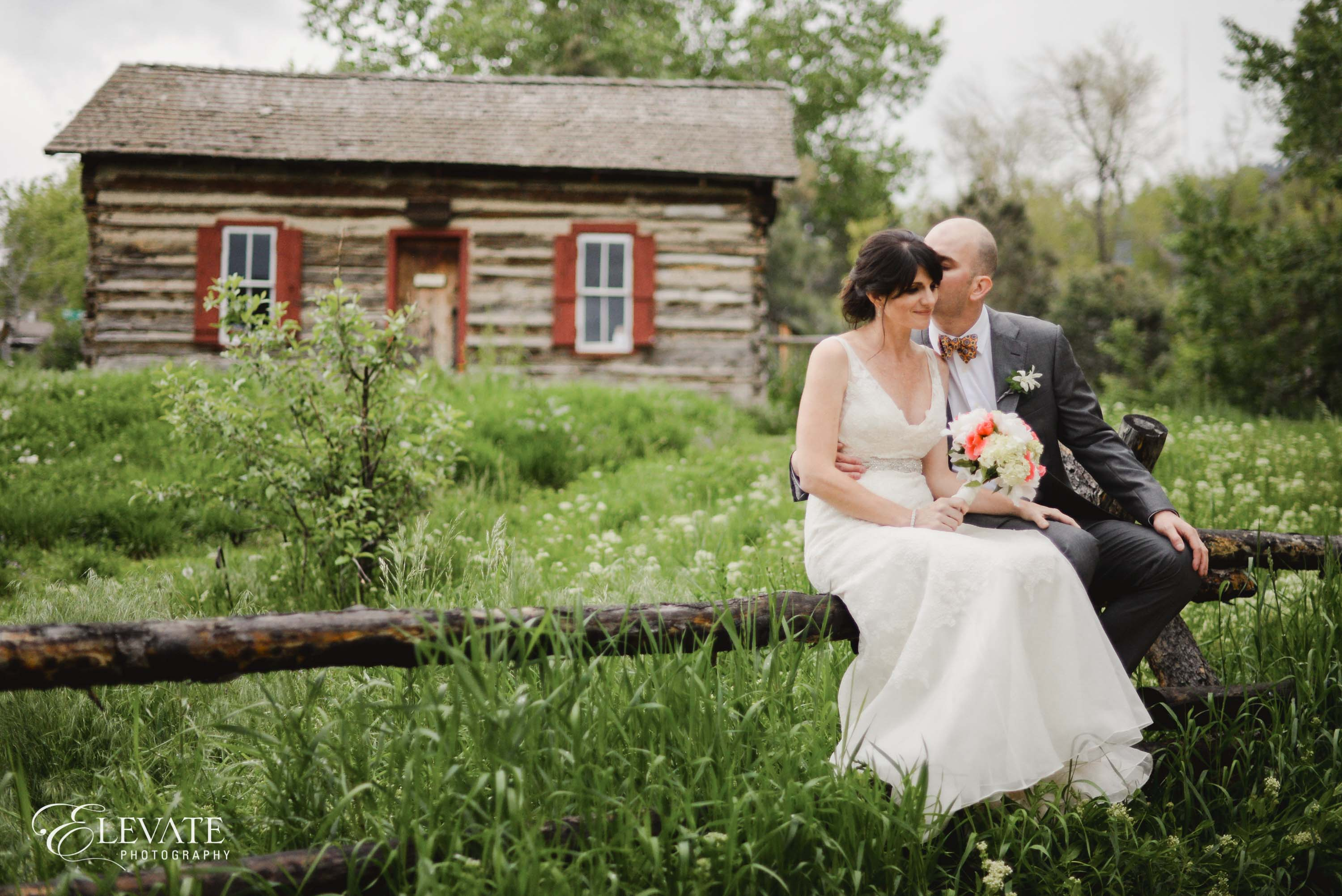 bride and groom on fence at clear creek history park