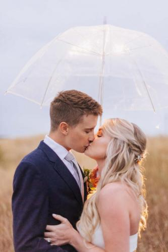 couple kissing with umbrella