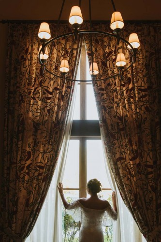 Bride posing at window with grand curtains and chandelier