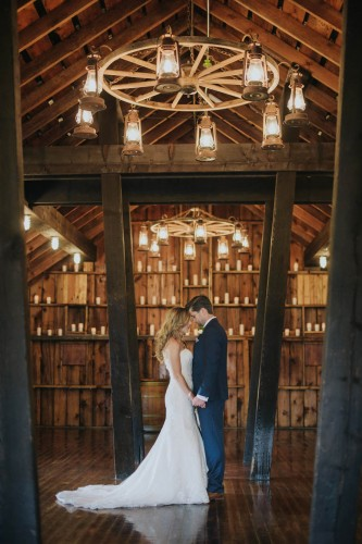 couple holding hands in barn