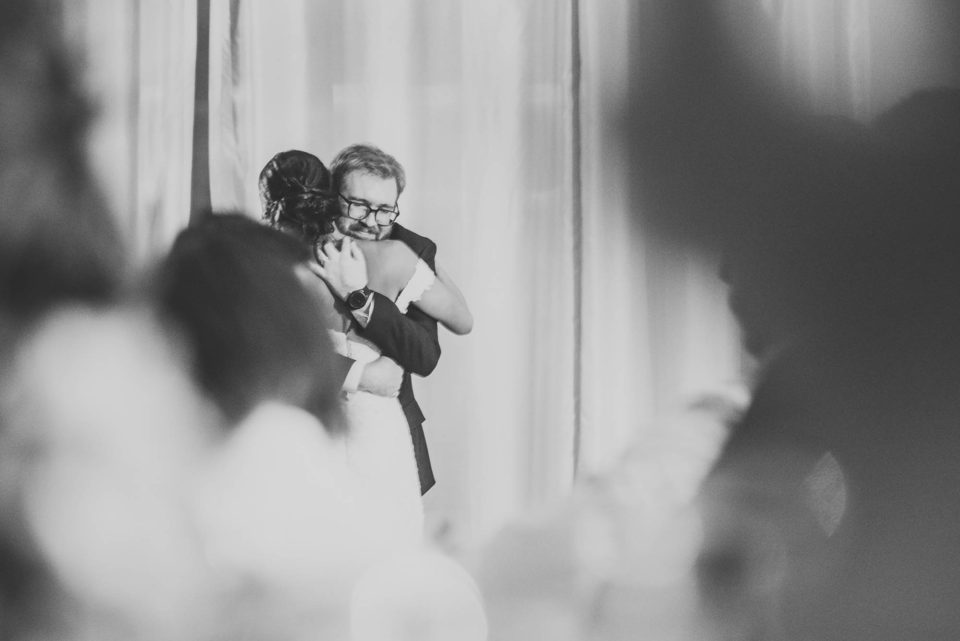 black and white bride groom reception hug